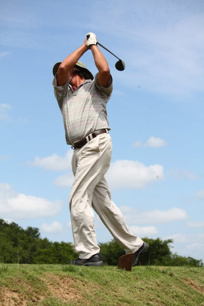 man in gray polo shirt and pants playing golf